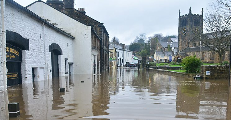 Image of a flooded village, including houses, pub and church